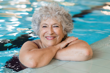 Photo pour Portrait of elderly woman against the edge of a swimming pool and looking at camera. Fit and active senior woman enjoying retirement in the swimming pool. Beautiful mature woman relaxing in the swimming pool. - image libre de droit