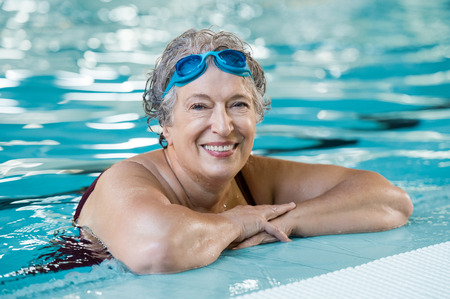 Foto de Mature woman wearing swim goggles at swimming pool. Fit active senior woman enjoying retirement standing in swimming pool and looking at camera. Happy senior healthy old woman enjoying active lifestyle. - Imagen libre de derechos