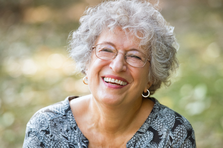 Foto de Portrait of senior woman smiling and looking at camera. Cheerful mature woman wearing eyeglasses in the park. Happy old woman with grey hair smiling. Carefree and positive retired woman. - Imagen libre de derechos