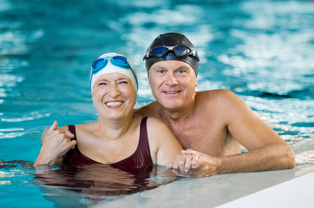 Photo for Portrait of a senior couple bathing in swimming pool and looking at camera. Smiling mature man and old woman enjoying time together in a swimming pool. Happy retired couple after aqua fitness. - Royalty Free Image