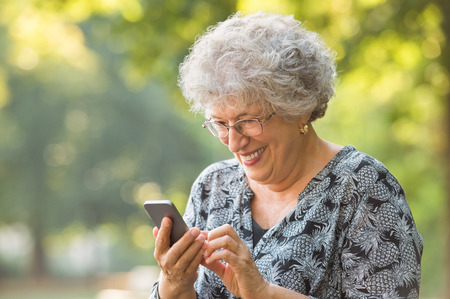 Foto de Smiling elderly woman wearing spectacles and typing phone message while sitting at park. Cheerful senior woman using wireless internet connection on smart phone while writing a sms. Happy elderly woman looking at screen on smartphone. - Imagen libre de derechos