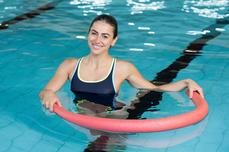 Photo for Happy smiling woman doing exercise with aqua tube in a swimming pool. Young sportive woman exercising in swimming pool with the help of a tube. Young heallthy woman doing aerobics in swimming pool. - Royalty Free Image