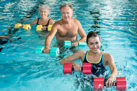 Foto de Happy active fitness mature man and senior woman doing exercise with aqua dumbbell in a swimming pool with instructor. Retired people doing aqua gym exercise with water dumbbell in swimming pool and looking at camera. - Imagen libre de derechos