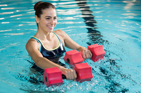 Photo pour Fit woman working out with foam dumbbell in swimming pool at leisure center. Woman engaged in doing aqua aerobics in water. Young beautiful woman doing aqua gym exercise with water dumbbell in swimming pool. - image libre de droit