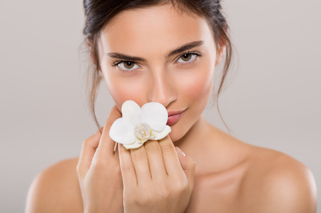 Photo pour Portrait of a beautiful woman with bare shoulders holding a flower of orchid isolated on grey background. Portrait of natural beauty of young woman holding white orchid flower near face and looking at camera. - image libre de droit