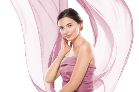 Photo pour Portrait of a young beautiful woman wrapped in violet cloth isolated on white background. Young pure woman looking at camera with hand on cheek. Glamour girl with pink flowing scarf with copy space. - image libre de droit