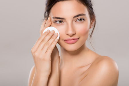 Foto de Healthy fresh girl removing makeup from her face with cotton pad. Beauty woman cleaning her face with cotton swab pad isolated on grey background. Skin care and beauty concept. - Imagen libre de derechos