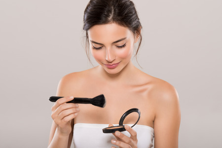 Photo pour Portrait of a young beautiful woman applying foundation with black brush. Young woman holding face powder box on grey background. Woman holding make up blush and smiling. - image libre de droit
