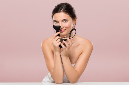 Photo pour Young beautiful woman holding foundation box and brush while leaning on white table. Smiling woman holding blusher box isolated on pink background. Beauty brunette girl having fun and joking with make up and face powder. - image libre de droit