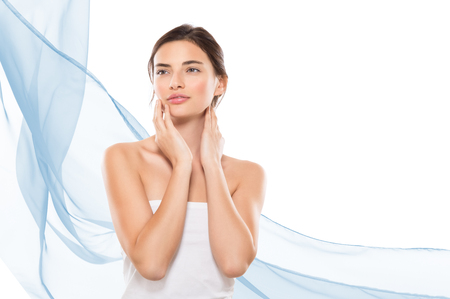 Photo pour Young woman looking away while touching her face isolated on white background. Beauty brunette girl feeling fresh after spa treatment with copy space on right side and blue waves of cloths. Beauty and skincare therapy. - image libre de droit