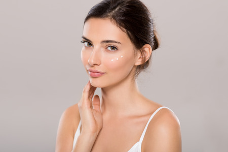 Photo pour Young woman applying moisturizer on face isolated on grey background. Beautiful woman applying cosmetic cream on skin near eyes and looking at camera. Beauty and skin care concept. - image libre de droit