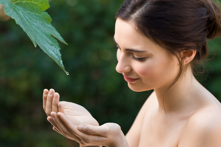 Photo pour Beautiful young woman take a drop of clear water from a leaf in the nature. Natural beauty refresh herself with water directly from a vine leaf. Symbol of purity, body care and nature harmony. - image libre de droit