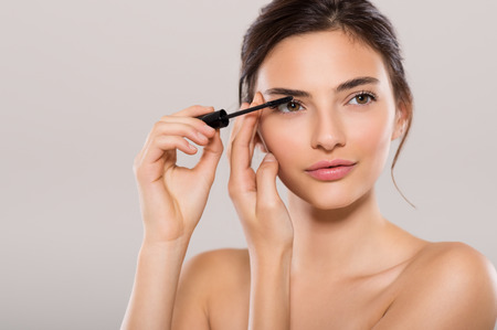 Photo pour Woman applying black mascara on eyelashes with makeup brush. Young beautiful woman applying mascara makeup on eyes by brush. Portrait of brunette beauty girl applying makeup over grey background. - image libre de droit