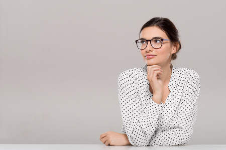 Foto de Beautiful young businesswoman wearing glasses and thinking with hand on chin. Smiling pensive woman with eyeglasses looking away isolated on grey background. Fashion and contemplative girl smiling and meditating on project. - Imagen libre de derechos