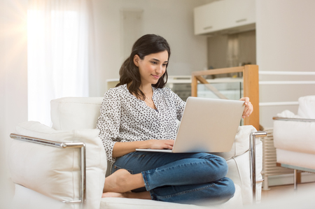 Photo pour Young woman doing research work for her business. Smiling woman sitting on sofa relaxing while browsing online shopping website. Happy girl browsing through the internet during free time at home. - image libre de droit