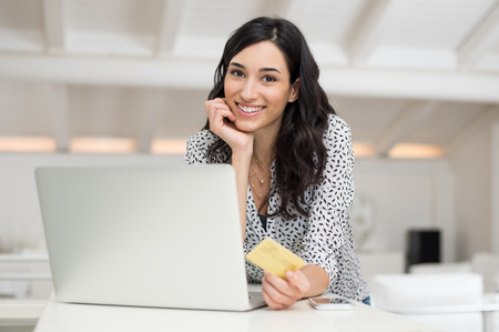 Photo pour Young happy woman doing shopping online with her laptop at home. Portrait of smiling woman in casual holding credit card and looking at camera. Beautiful girl paying online bills using gold card. - image libre de droit