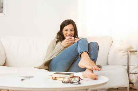 Photo for Happy woman sitting on couch holding a cup of tea in living room. Portrait of a young woman drinking a cup of coffee while relaxing on sofa at home. Smiling girl with woolen jacket drinking hot coffee and looking at camera. - Royalty Free Image