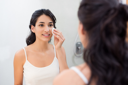 Photo pour Healthy fresh girl removing make up from her face with cotton pad. Smiling girl cleaning her face in bathroom. Beautiful healthy woman making scrub on her face. - image libre de droit