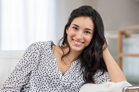 Photo pour Closeup of a smiling young woman looking at camera. Portrait of happy brunette girl smiling at home. Relaxed woman at home smiling. - image libre de droit