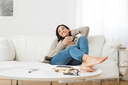 Foto de Young smiling woman sitting on sofa and looking up while drinking hot tea. Young brunette woman thinking at home in a leisure time. Happy girl relaxing at home on a bright winter morning. - Imagen libre de derechos