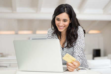 Foto de Happy young woman holding a credit card and shopping online at home. Beautiful girl using laptop to shop online with creditcard. Smiling woman using laptop and credit card for online payment. - Imagen libre de derechos