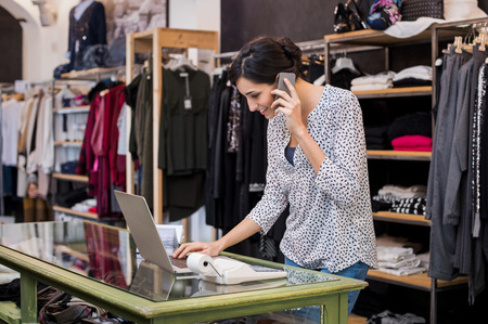Foto de Young businesswoman talking over phone while checking laptop in her clothing store. Young entrepreneur in casual using laptop and talking on mobile. Store manager woman checking important documents on laptop. Small business concept. - Imagen libre de derechos