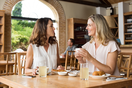 Photo pour Two beautiful mature women holding cup of coffee and talking to each other in a cafeteria. Senior women in conversation while having breakfast. Happy middle aged friends meeting up for coffee. - image libre de droit