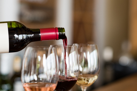 Foto de Pouring red wine from bottle into the wineglass on bar. Close up of red wine pouring from bottle to glass in a winery. Wine tasting in a winehouse. - Imagen libre de derechos
