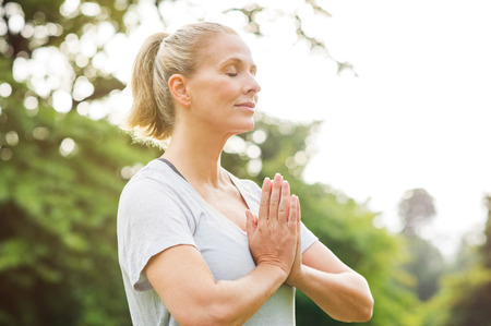 Foto de Mature woman in park joining hands with closed eyes and meditates. Relaxed senior woman with joined hands breath deeply with closed eyes. Healthy woman meditating outdoor. - Imagen libre de derechos