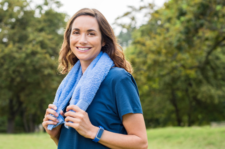 Foto de Happy mature woman smiling at park after exercise. Portrait of middle aged woman with blue towel around neck looking at camera. Beautiful mature woman feeling energetic after yoga and exercise outdoor. - Imagen libre de derechos