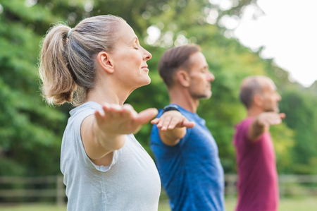 Photo pour Group of senior people with closed eyes stretching arms at park. Happy mature people doing yoga exercise outdoor on a bright morning. Yoga class with woman and men doing breath exercising with stretched arms. - image libre de droit