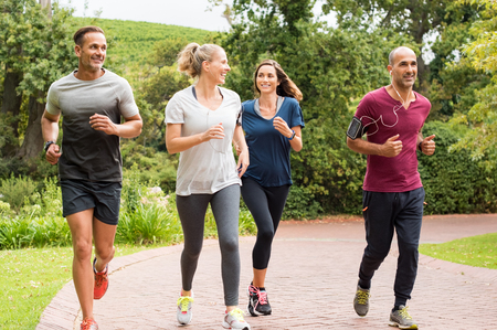 Foto de Healthy group of people jogging on track in park. Happy couple enjoying friend time at jogging park while running. Mature friends running together outdoor. - Imagen libre de derechos