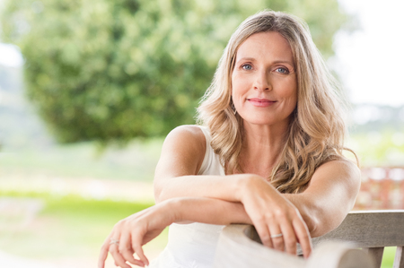 Photo for Happy senior woman relaxing on bench in the lawn. Close up face of a mature blonde woman smiling and looking at camera. Retired woman in casuals sitting outdoor in a summer day. - Royalty Free Image