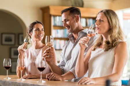Foto de Mature friends tasting red and white wine at vineyard. Senior couple and visitor drinking white wine. Customers at a bar winetasting and talking to each other. - Imagen libre de derechos