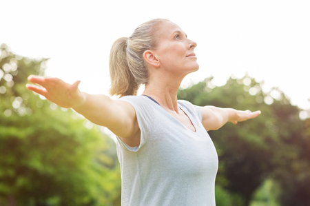 Photo for Mature woman doing yoga at park and looking away. Senior blonde woman enjoying nature during a breathing exercise. Portrait of a fitness woman stretching arms and looking away outdoor. - Royalty Free Image
