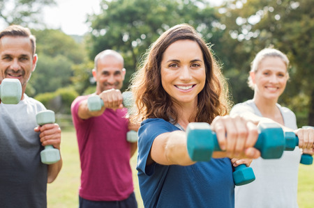 Foto de Mature people in training session of aerobics using dumbbells at park. Happy man and smiling woman practicing fitness together outdoor. Portrait of mature woman doing exercise with other people in background. - Imagen libre de derechos
