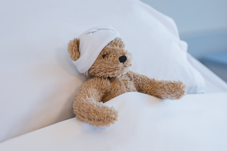Foto de Injured teddy bear sleeping on hospital bed. Brown plush toy with a headache resting on bed. Sick brown bear with a bandage on his head lying in bed hospitalized at medical clinic. - Imagen libre de derechos