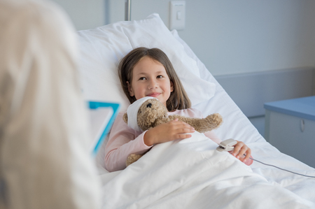 Photo pour Smiling little girl with oxygen saturated probe resting on hospital bed. Girl patient looking at doctor with a smile. Child and doctor at medical clinic. - image libre de droit
