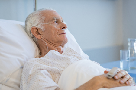 Photo for Sad senior man lying on hospital bed and looking away. Old patient with oxygen tube feeling lonely and thinking at hospital. Sick aged man lying hospitalized in a medical clinic. - Royalty Free Image