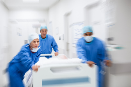 Foto de Nurse and doctor in a hurry taking patient to operation theatre. Patient on hospital bed pushed from surgeon to emergency theatre. Team of doctors and surgeon rushing patient. - Imagen libre de derechos