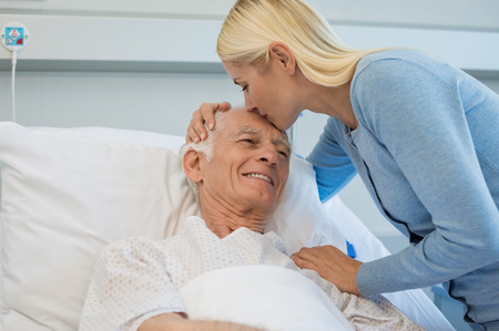 Photo pour Young daughter kissing senior father on forehead in hospital bed. Cheerful old dad patient being kissed by daughter while recovering from disease in clinic. Lovely woman visiting old father at medical clinic. - image libre de droit