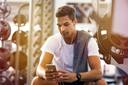 Photo pour Young handsome man using phone while having exercise break in gym. Muscular guy using smartphone sitting on the bench after the daily training. Latin man listening to music while resting after exercise. - image libre de droit