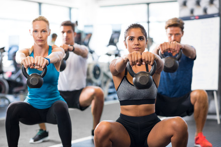 Photo pour Women and men exercising with kettlebells in gym. Group of young people doing a kettle bell exercise along with squatting. Fitness class and girls training by weights. - image libre de droit