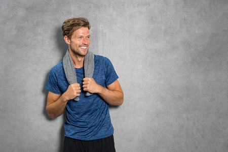 Photo pour Portrait of a smiling fitness man with towel on shoulders looking away. Happy young man relaxing after training and leaning on grey wall. Sporty active guy resting after workout with copy space. - image libre de droit
