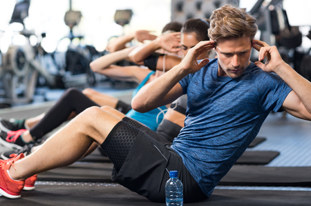 Foto de Muscular guy doing sit ups at gym with other people in background. Young athlete doing stomach workout in modern gym. Handsome fit man doing crunches at gym. - Imagen libre de derechos