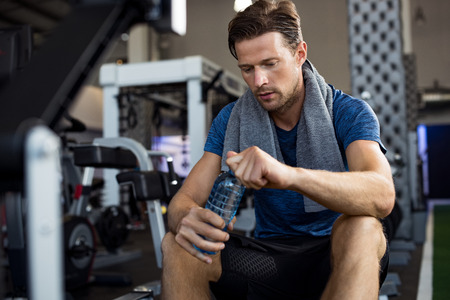 Photo for Young man with towel on his shoulders drinking water while sitting at gym. Sweaty guy opening cap of bottle to drink water after workout. Tired man resting after training and holding bottle of water. - Royalty Free Image