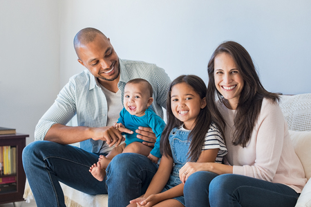 Photo pour Portrait of happy multiethnic family sitting on sofa at home. Smiling couple with kids sitting on couch and looking at camera. Black father and latin woman with daughter sitting on couch and having fun. - image libre de droit