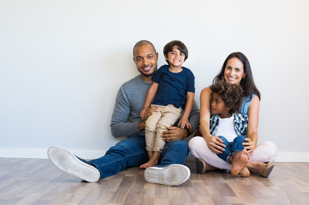 Foto de Happy multiethnic family sitting on floor with children. Smiling couple sitting with two sons and looking at camera. Hispanic mother and black father relaxing with their cute boys leaning on wall with copy space. - Imagen libre de derechos