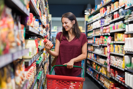 Photo pour Happy mature woman looking at product at grocery store. Smiling hispanic woman shopping in supermarket and reading product information. Costumer buying food at the market. - image libre de droit