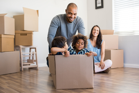 Foto de Happy african american father playing with children sitting in carton box at new home. Happy multiethinc family enjoying new home. Young parents and sons having fun during moving house. - Imagen libre de derechos
